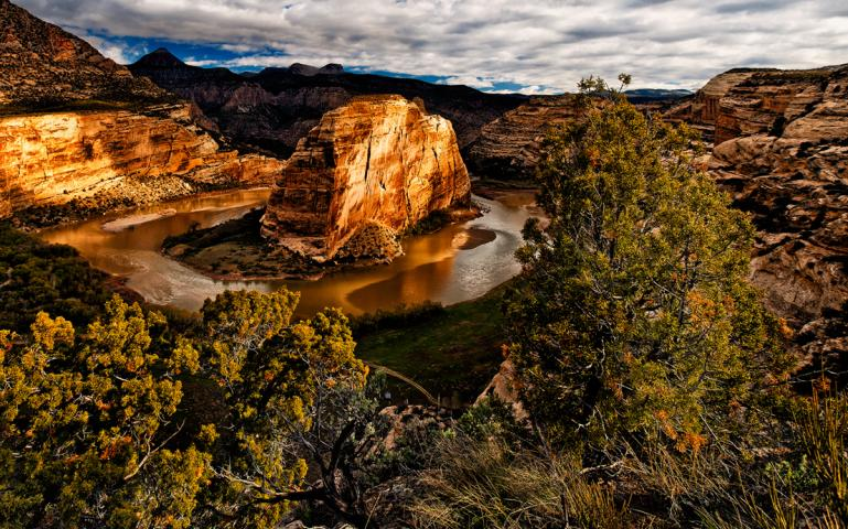 After merging with the Yampa River, the Green River takes a U-turn around the monumental ridge of sandstone called Steamboat Rock.