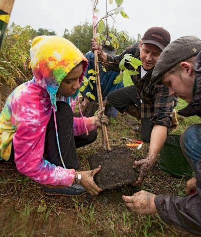 Green Mountain College students plant trees to form a riparian buffer along the Poultney River.