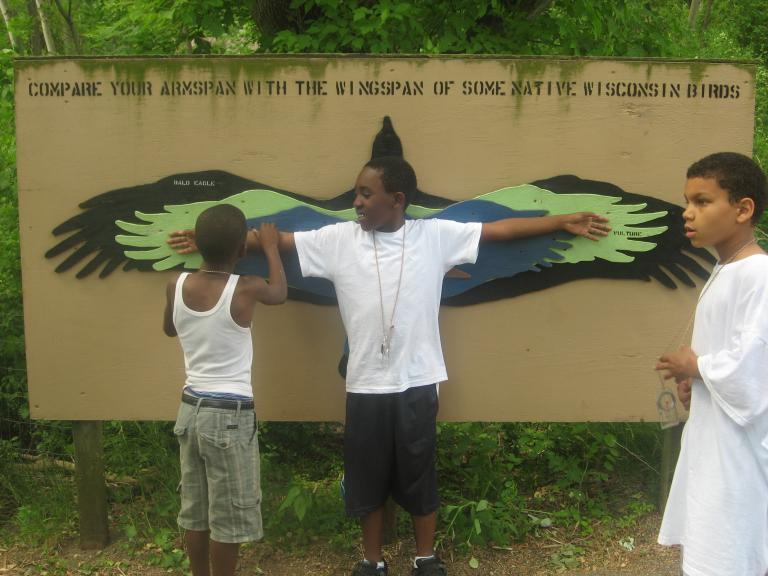 ICO youth measures his wingspan.
