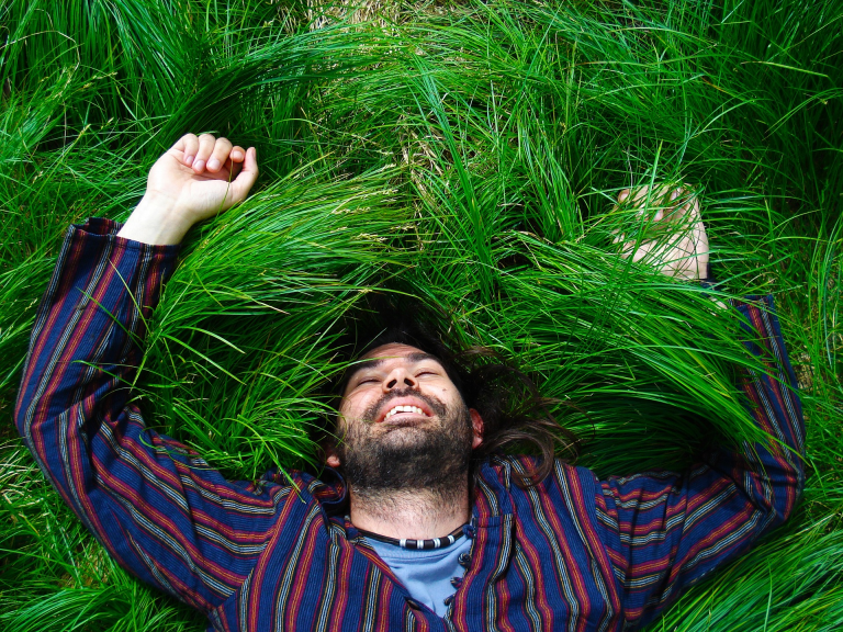 A bearded man smiling and resting with arms above his head in tall, deep green grass