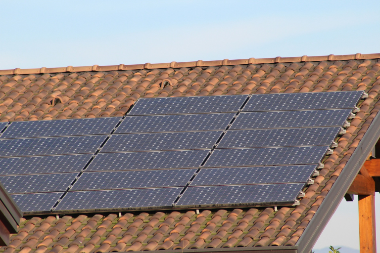 Solar panels installed on a clay tile roof in the sun