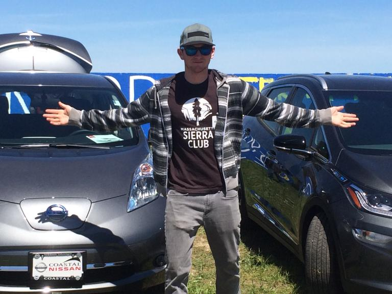 A fashion forward visitor in a Sierra Club t-shirt posing with electric vehicles