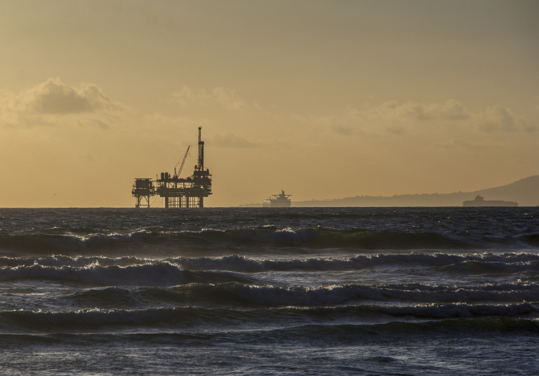 Offshore oil rig silhouetted at sunset
