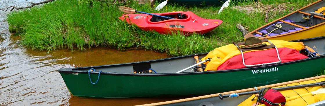 Canoes and kayaks line the riverbank during a paddling break