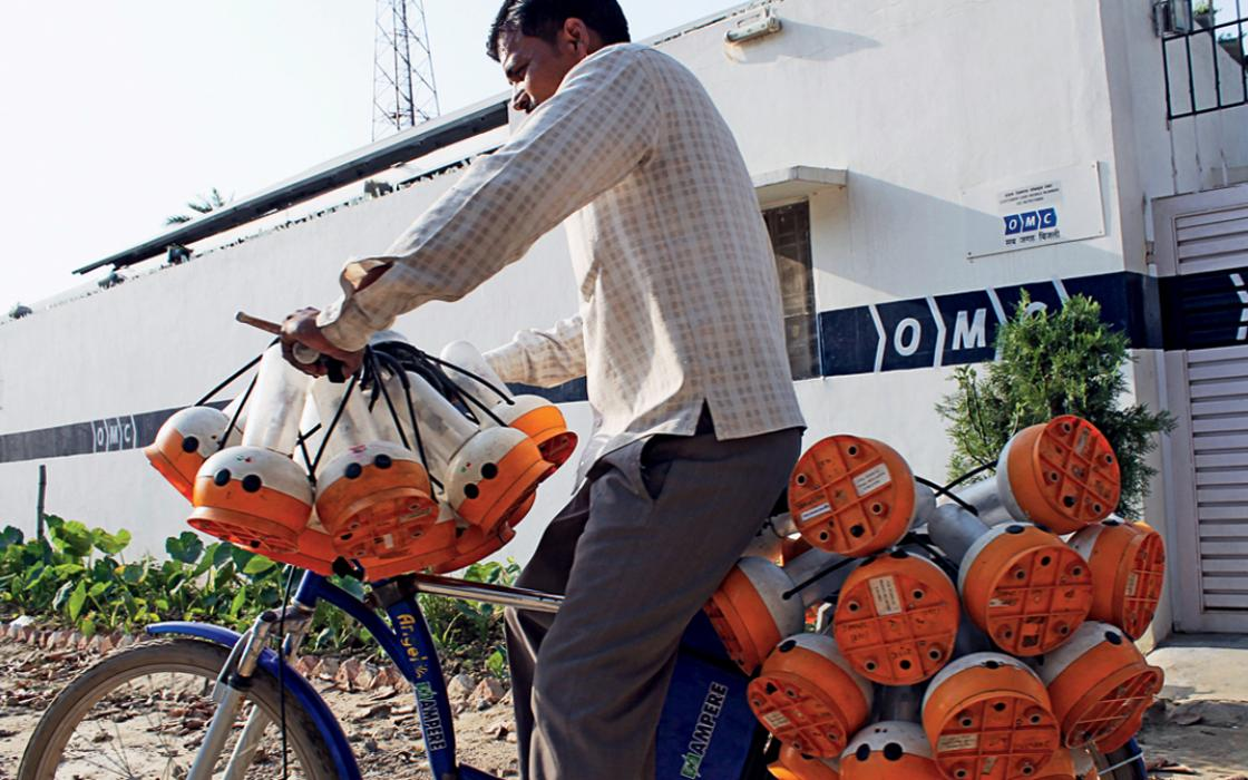 A deliveryman leaves OMC's Jangaon plant on a bike loaded with fully charged lanterns. In the background, a telecom tower operates  on solar energy provided by the same plant.