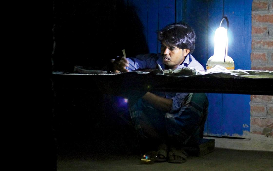 Sufiyan, a 32-year- old embroiderer, regularly stitches until midnight beside a  solar-charged lantern.