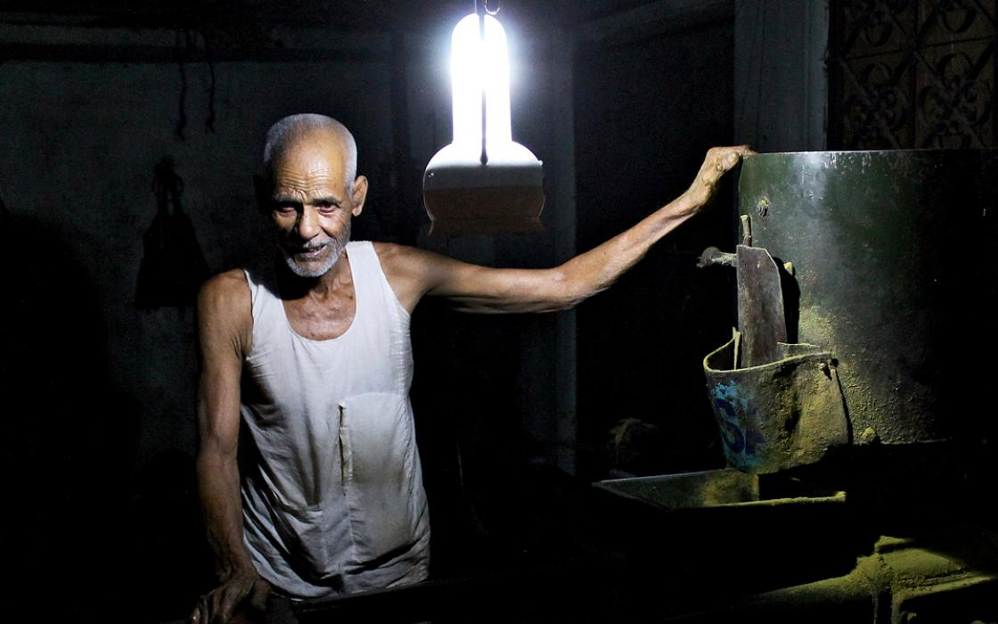 A mustard grinder works by the light of a solar-charged lantern.