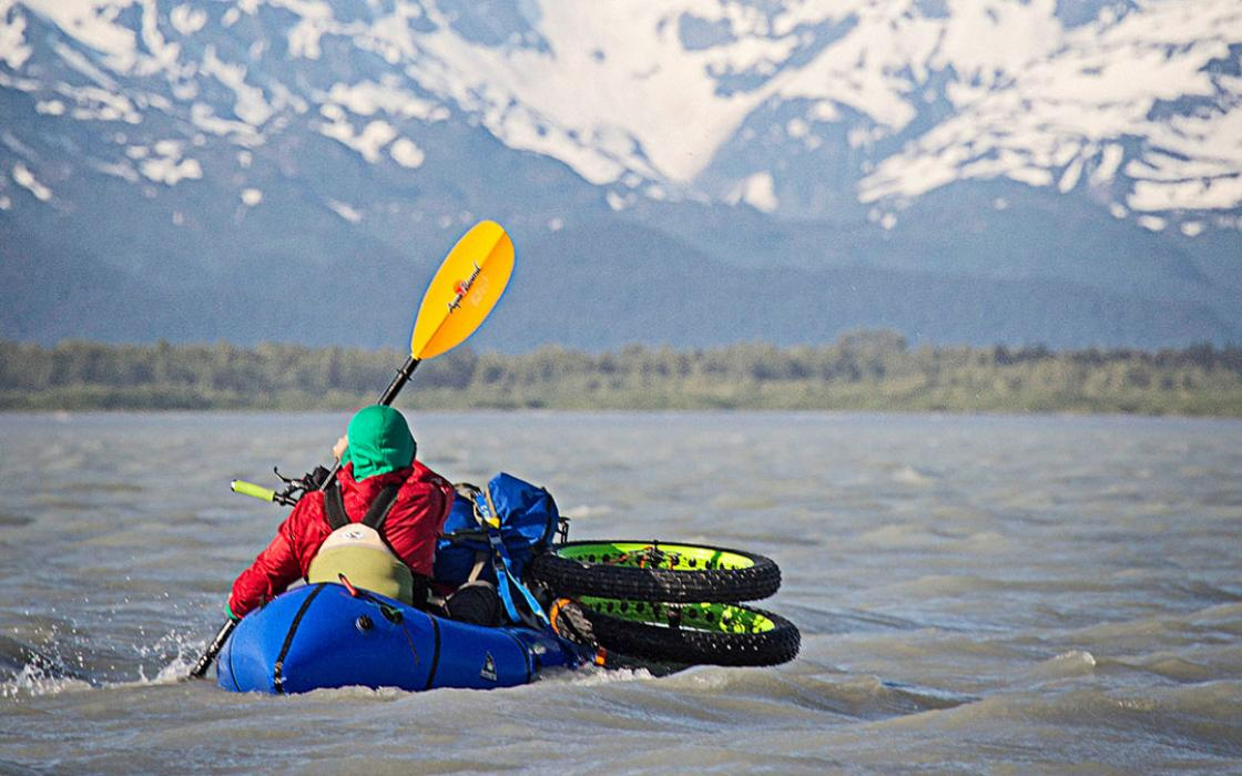 Ryan Krueger's wheels, rigged onto his packraft, are lapped by the Dangerous River
