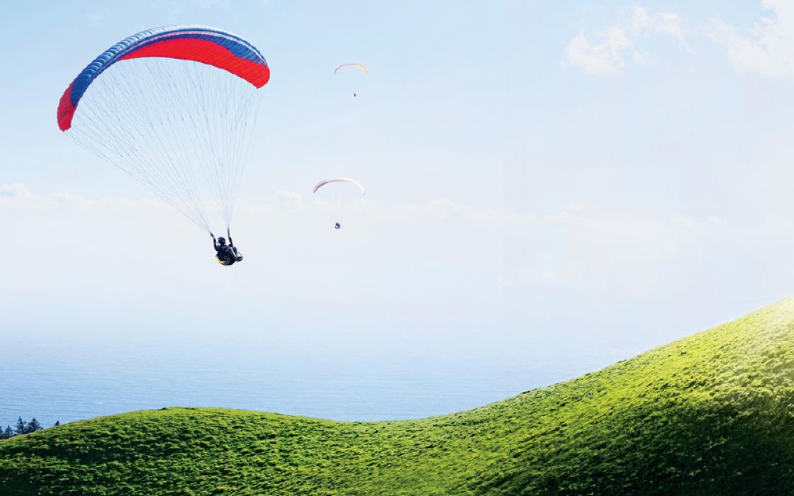 Three paragliders descend along the curvy flanks of Mt. Tamalpais in Marin County, California, overlooking the Pacific Ocean.