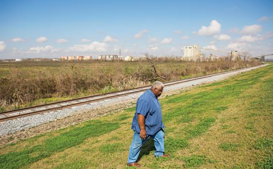 Wilkey Declouet walks by the levee near the proposed RAM coal terminal site, about a half mile away from Ironton, Louisiana.