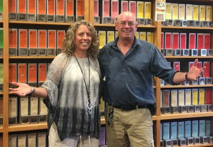 Kari Grady Grossman and George Grossman, Owners of Happy Lucky's Teahouse, stand together with their arms out in front of shelves of tea
