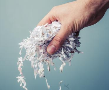 A hand holds shredded paper that can be composted.