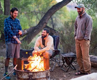 Veterans Kajetan Bauer, Brandon Lay, and Armando Medina sit around a campfire near Cedar Mesa, Utah.