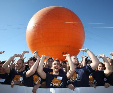 """West Virginia University students—wearing T-shirts that say """"Preserving Energy with Appalachian Knowledge""""—at the 2013 Solar Decathlon at the Orange County Great Park (known for its giant orange balloon)."""