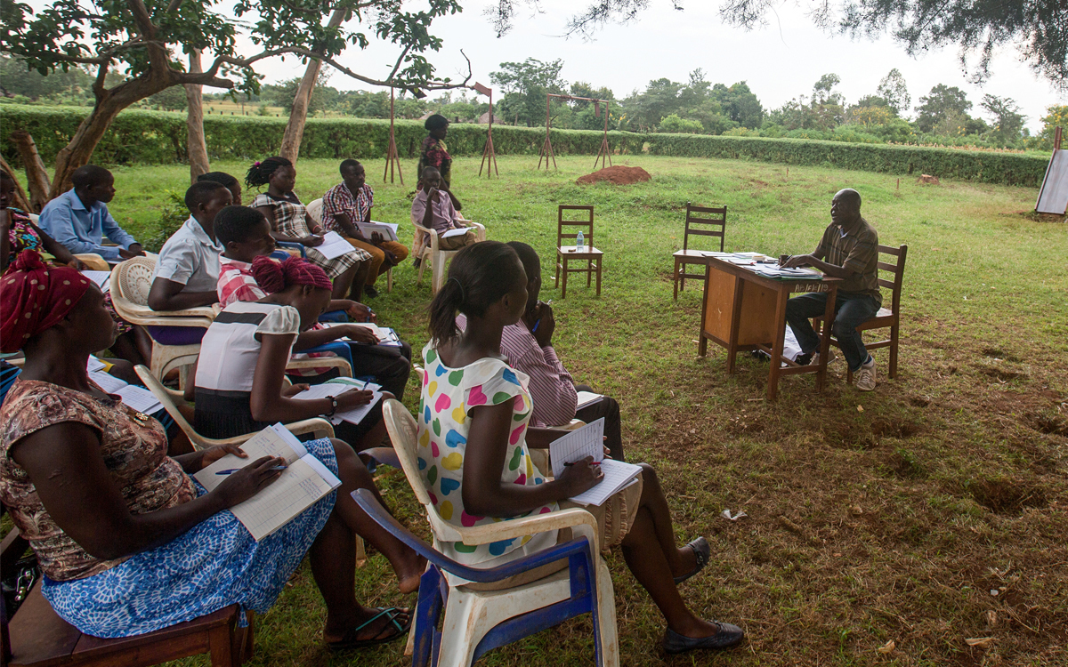 Stephen Okollet teaches an accounting class to a group of volunteers in Uganda.