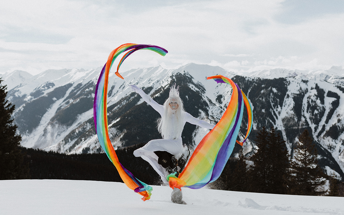 Pattie Gonia stands on top of a snowy mountain wearing all white (including a white wig) and holding up two large rainbow streamers.