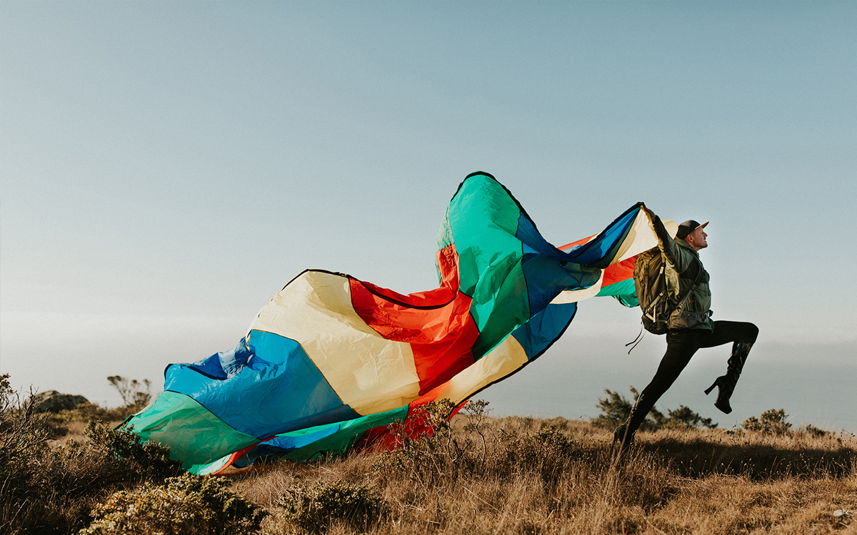 Pattie Gonia walks in high-heel black vinyl boots, black pants, and a green jacket. She's trailing a multi-colored tent or parachute behind her in a scrubby landscape.
