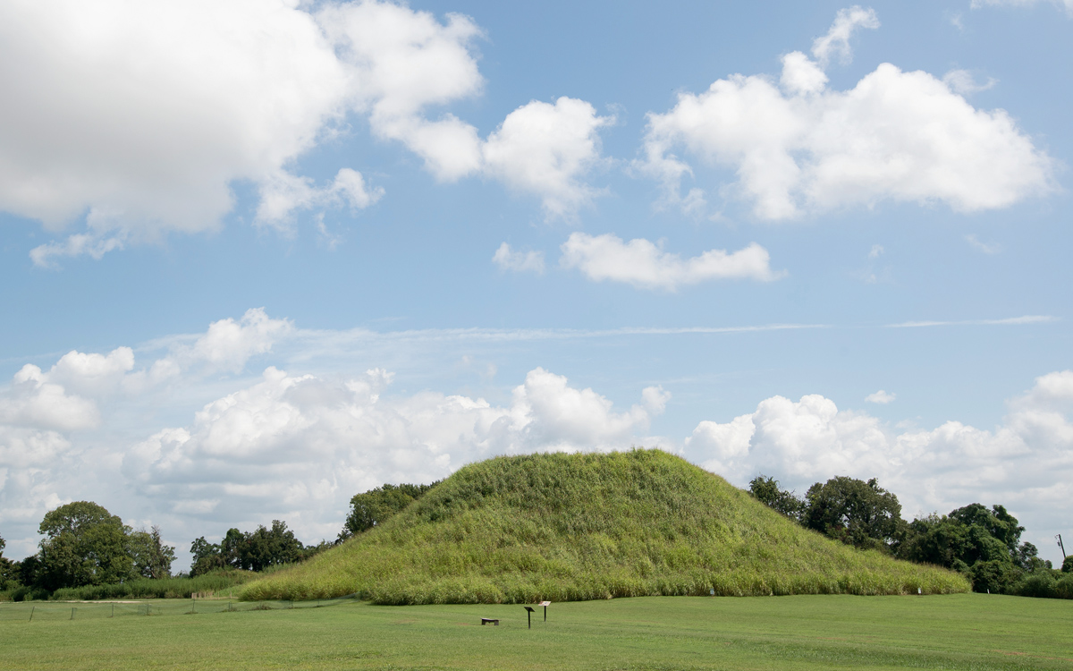 A large, grassy mound sits in a field below a blue sky and clouds at the Winterville Mounds site in Mississippi.