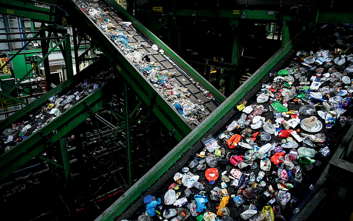 Three conveyor belts hold an assortment of crushed plastic waste in a Brooklyn recycling facility.