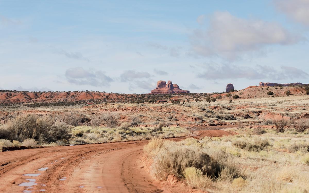 A dirt road curves through desert terrain in Cove, Arizona.