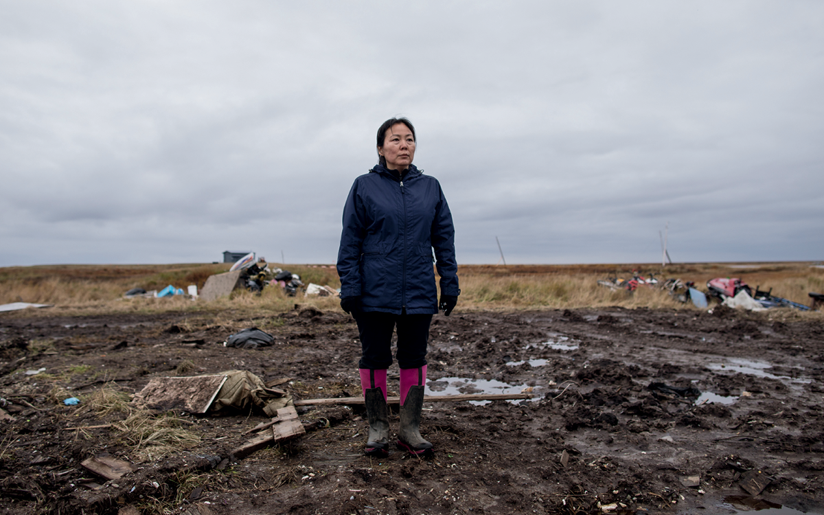 Charlene Carl, in waders, stands on muddy ground where her home used to be in Newtok, Alaska.