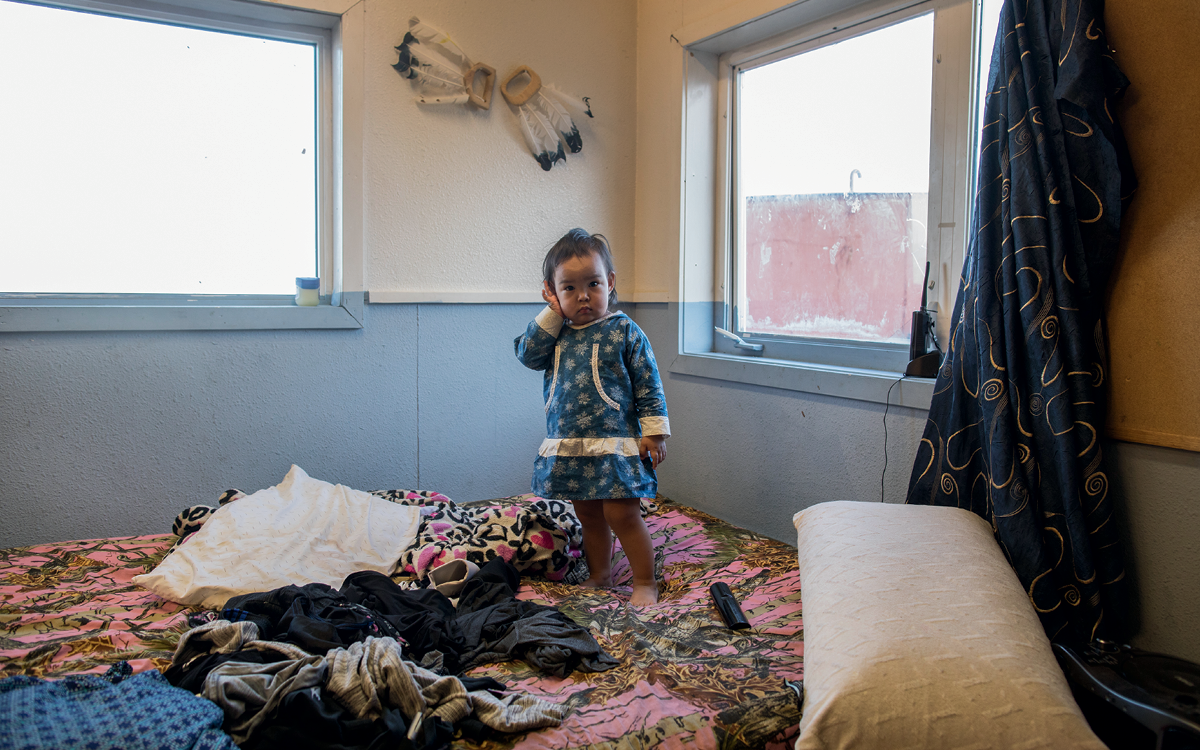 Katie Ayuluk's two-year-old daughter stands on a bed.
