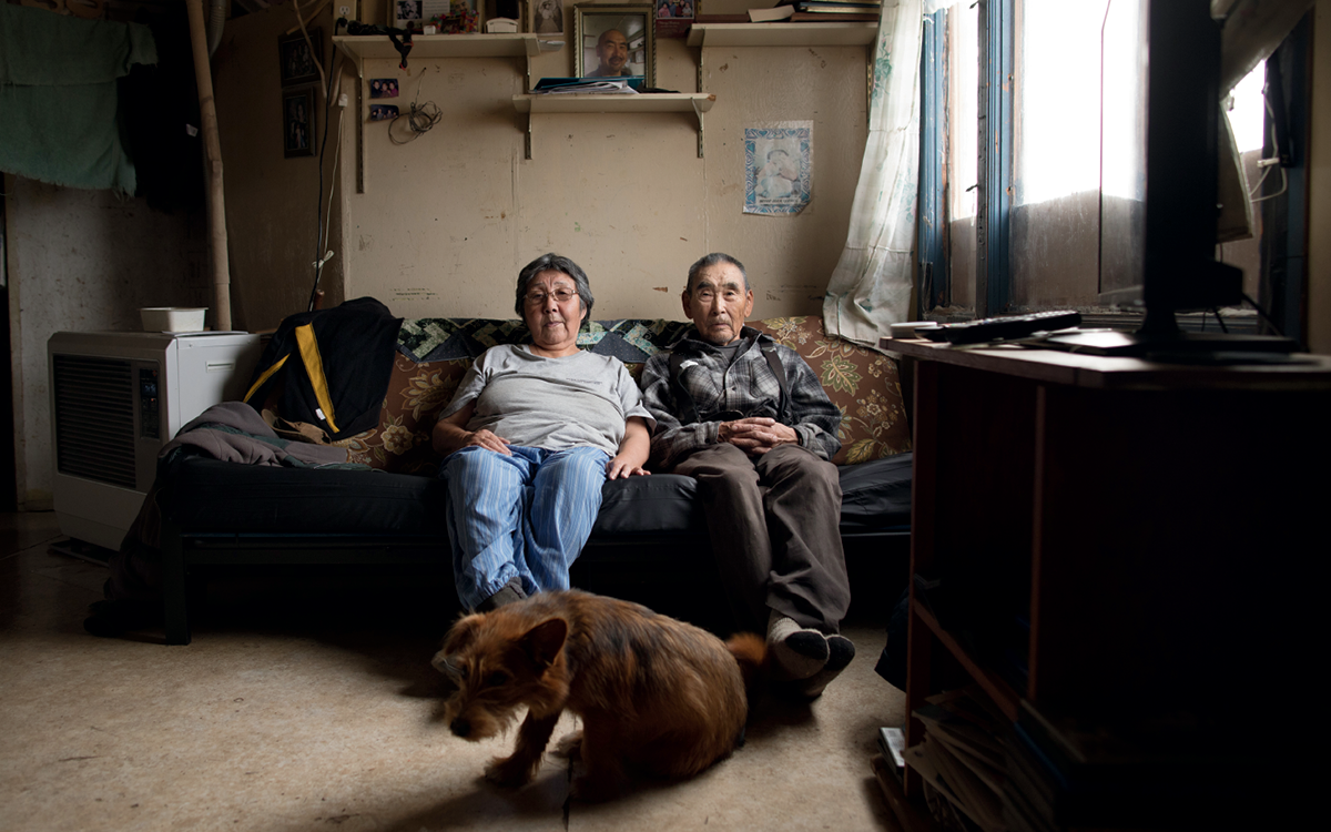 Newtok residents Mary and Mark George sit on a couch in their home. A dog sits nearby.