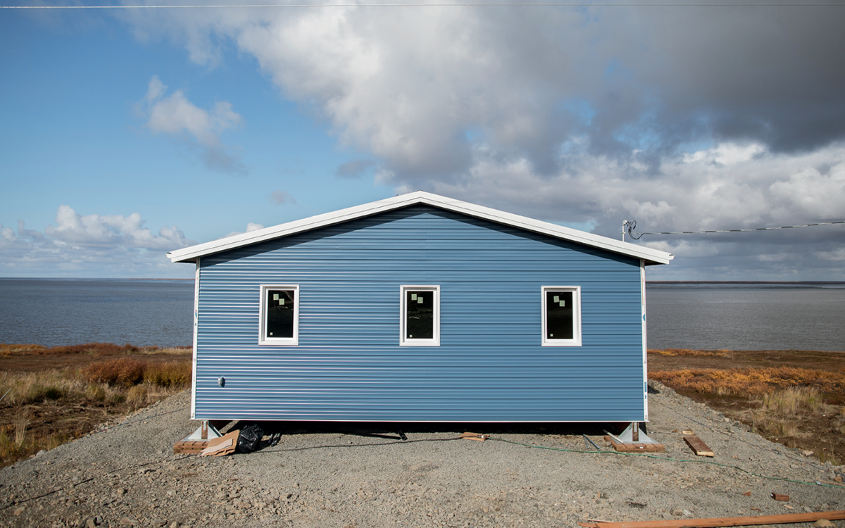 A newly build home in Mertarvik, Alaska. It's one story, blue with white trim, near the water.