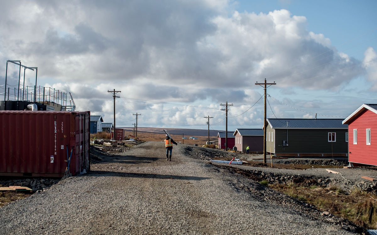 A construction worker walks down a gravel street in Mertarvik. New houses in bright colors appear on both sides.