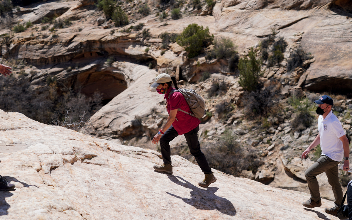 Deb Haaland wears jeans, hiking boots, and a baseball cap as she climbs up a rock. A man follows behind her.