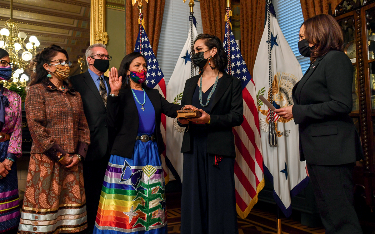Deb Haaland, wearing a bright-colored dress, has one hand on a bible and one palm in the air. All six people in the photo are wearing face masks.