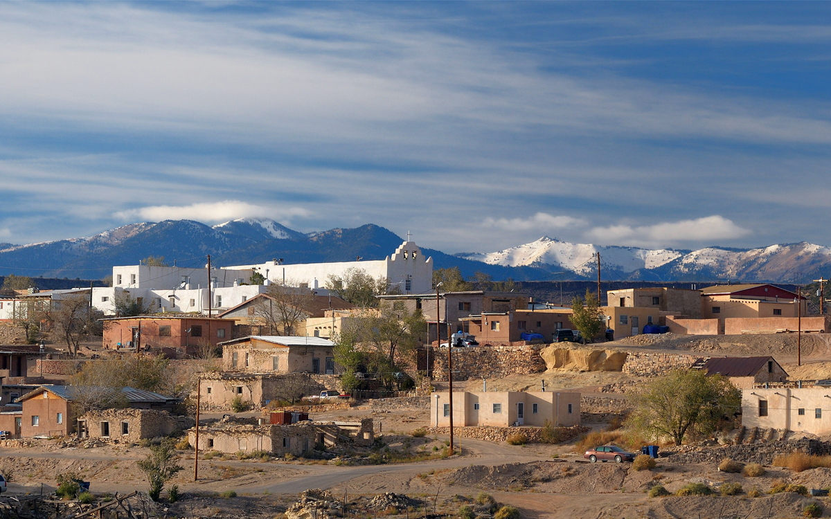 Photo of Laguna Pueblo shows several rows of brown and beige stone buildings. Behind them is a white church and snow-covered mountains in the background.