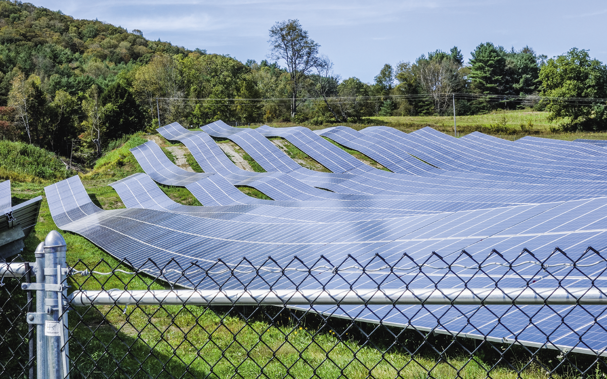 Twelve strips of undulating solar panels lie on the ground.