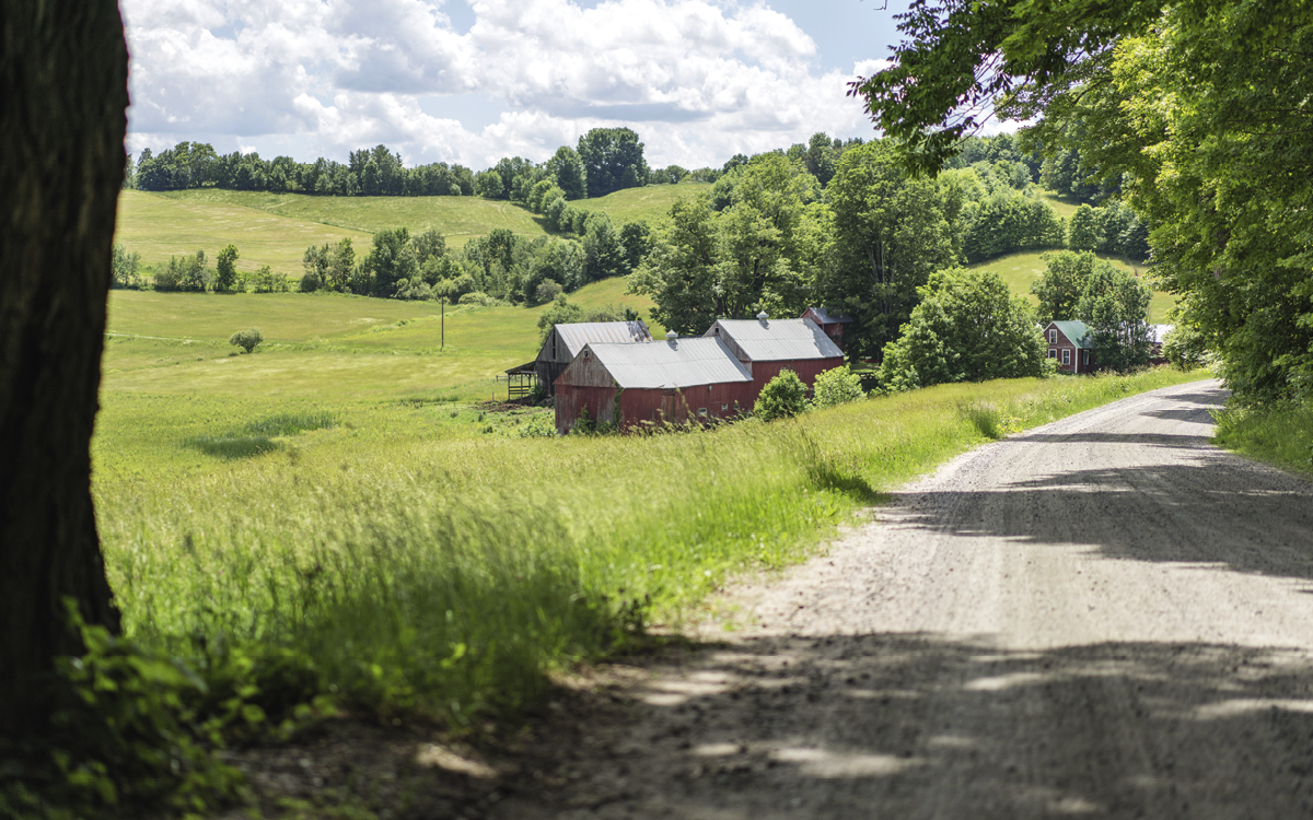 A red barn and a dirt road sit among rolling green hills.